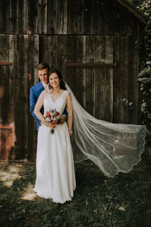 Hochzeitspaar vor Scheune Hochzeitsblume Brautkleid