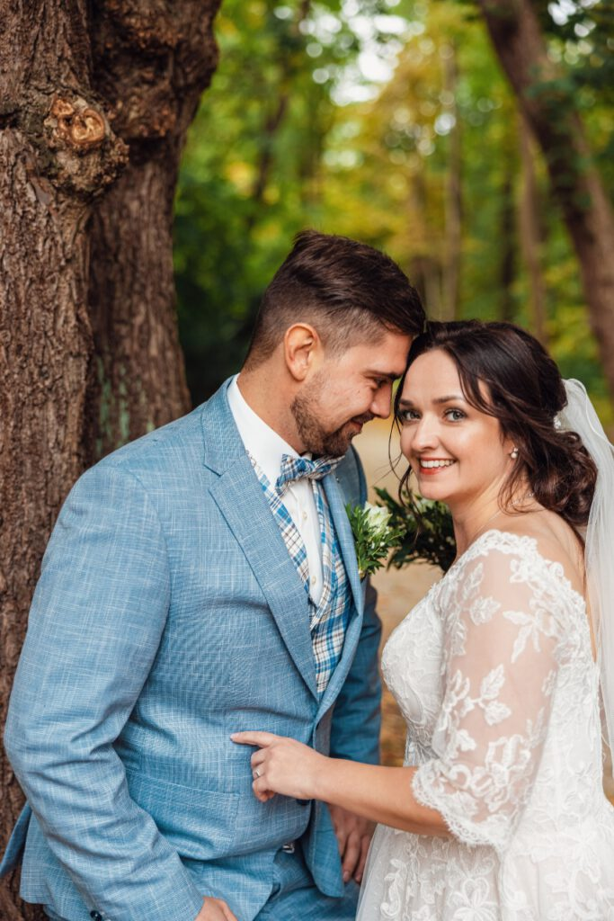 Brautpaar umarmt sich vor einem Baum